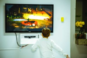 a child enjoying one of the best buy tvs in his home